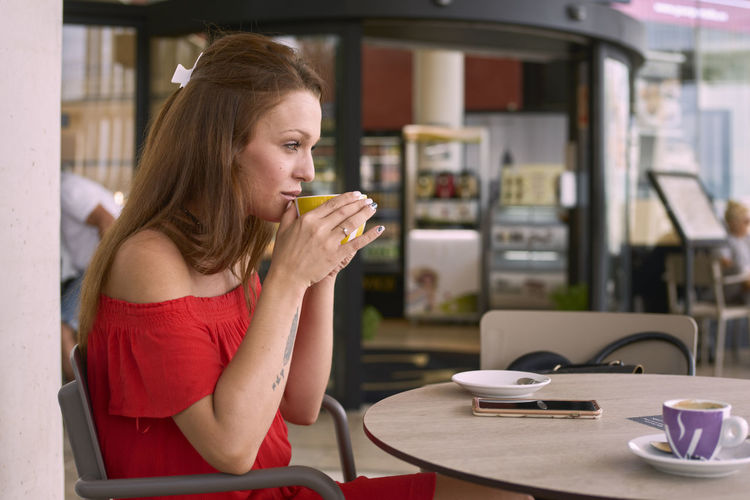 Young woman drinking coffee cup on table at cafe