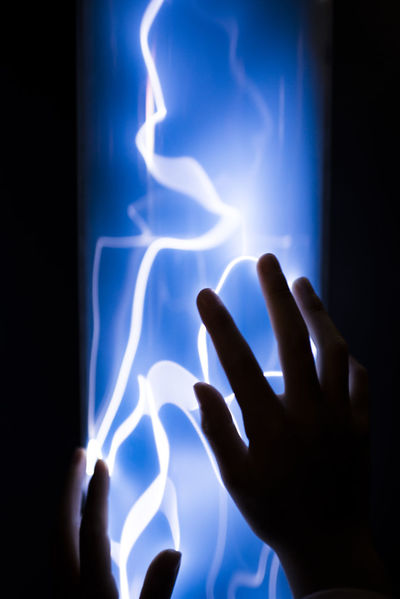 Human Hand Blue Illuminated Indoors  Light - Natural Phenomenon Unrecognizable Person Glowing Real People Touching Light Plasma Darkness Plasma Lamp Science Museum  Electricity  Visual Creativity Physics