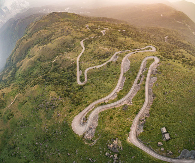 Aerial Angle View Of Winding Road Amidst Green Mountains
