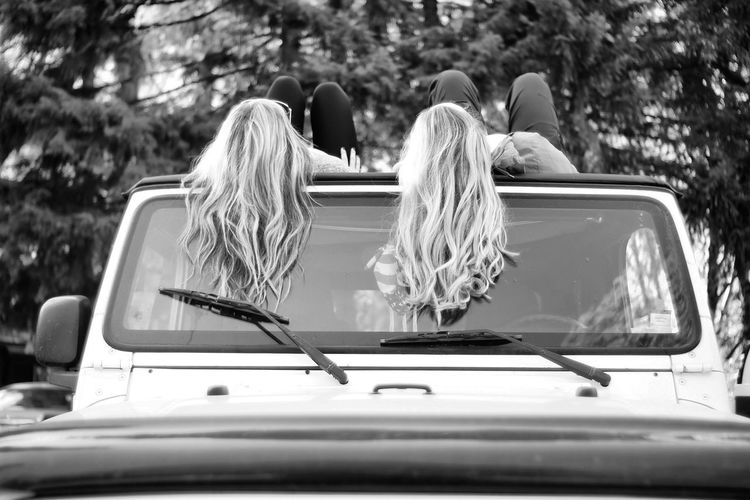 Low angle view of friends lying on car roof