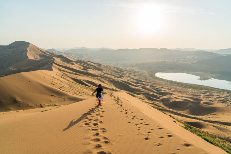 Rear view of woman walking on sand dune in badain jaran desert