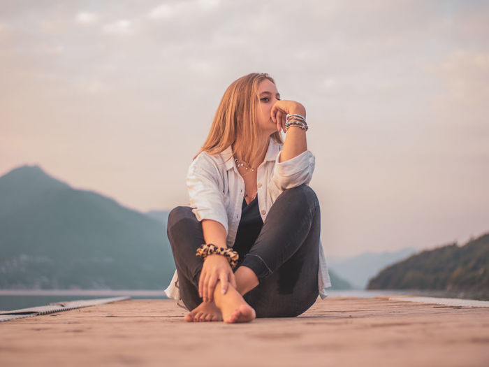 Young woman sitting on shore against sky during sunset