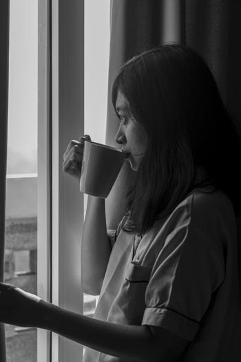 Side view of young woman drinking coffee