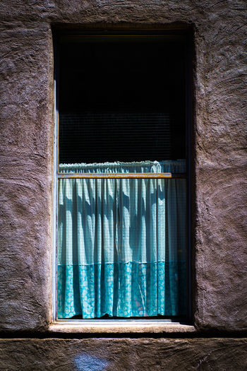 Close-up of window with blue curtain