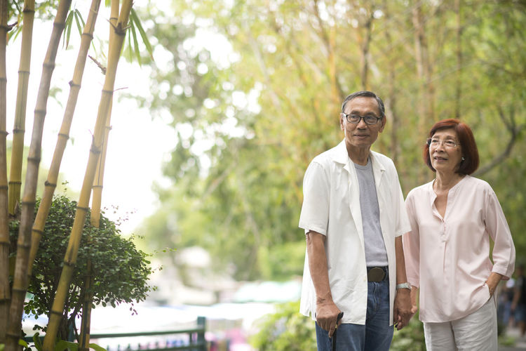 Senior Couple Standing By Railing Against Trees