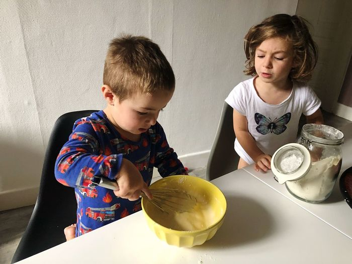 Cute siblings preparing food in kitchen