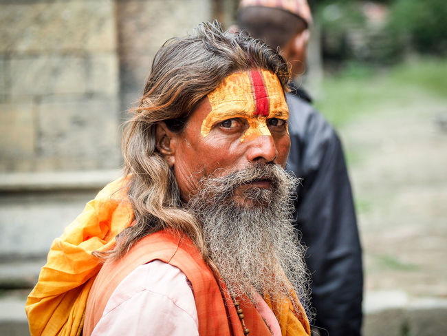 Hindhu holy man, a Sadhu, hanging out by the Pashupati temple in Kathmandu, where cremation rituals take place 24/7. Death is part of life in these parts and the normality of life prevails even when the rituals are running. Face Hindu Holydays Man Nepal Portrait Sadhu Travel