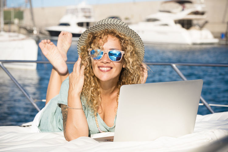 Portrait of smiling young woman using mobile phone in sea