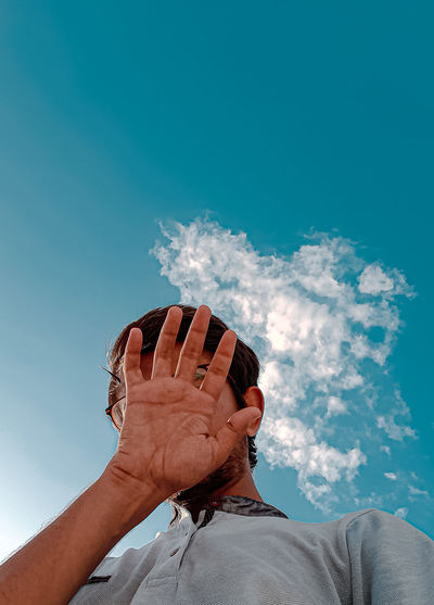 Low angle view of hand against sky