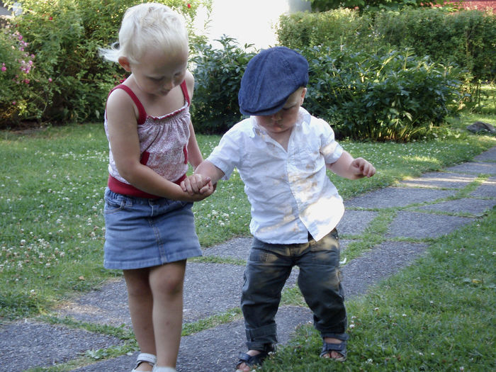 A young girl holding her baby brothers hand and helping him walk. Bonding Child Childhood Day Family Innocence Sibling Sister Togetherness Two People