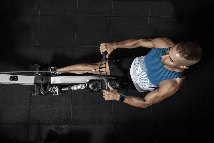 Directly above shot of determined disabled man exercising on rowing machine at gym