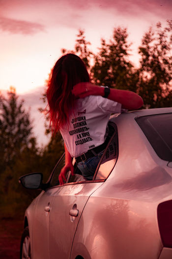 Rear view of woman against sky during sunset