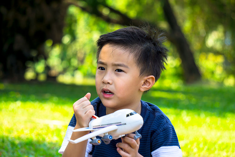 Close-Up Of Boy With Airplane Toy In Park