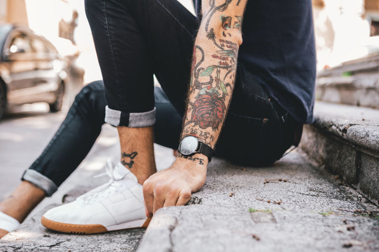 Young Man casually dressed wearing analog watch in the Urban environment Low Section Real People Men Tattoo Human Leg Human Body Part Shoe People Lifestyles Adult Selective Focus Day Body Part Two People Casual Clothing Leisure Activity Standing Women Hand Human Limb Human Foot Watch Wrist Watch Jewellery Jewelry Young Adult Young Men City City Life Urban Street