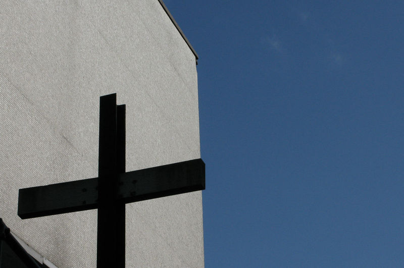 Low angle view of cross against concrete wall