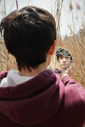 Rear view of young man looking at his reflection in mirror