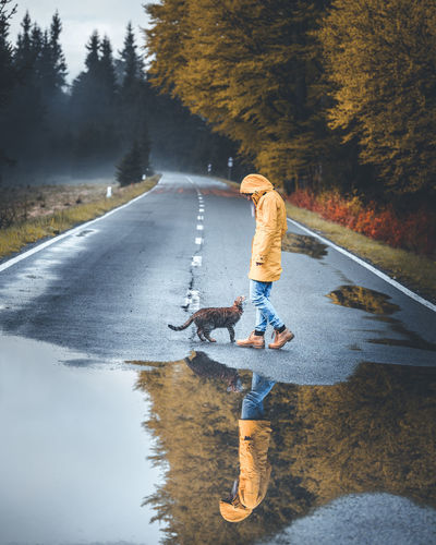 Side view full length of young woman standing by puddle and cat on road
