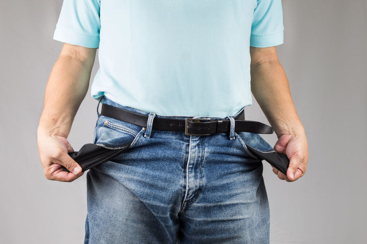 Hands pulling empty pockets from pants suggesting No Money or broke. Broke Adult Close-up Conceptual Empty Pockets Finance Hardship Jeans No Money One Man Only Pocket  Standing