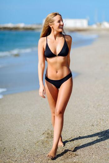 Cheerful young woman wearing bikini while walking at beach