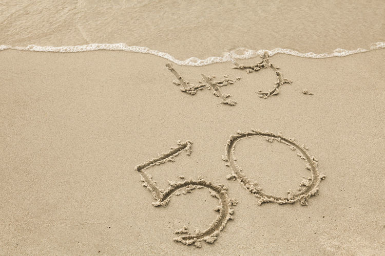 50th anniversary written in the sand of a beach 49 50 Surf Travel Wave Anniversary Beach Birthday Change Concept Drawing Fifty Greeting Card  Handwriting  Nature No People Outdoors Sand Sand Painting Sea Summer Tourism Vacation Water Wet