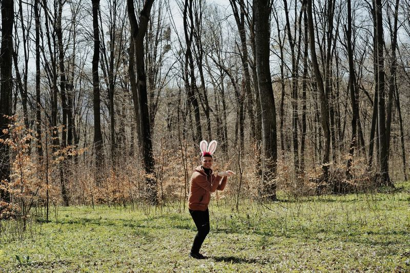 Young Man Wearing Bunny Ear Headband At Forest