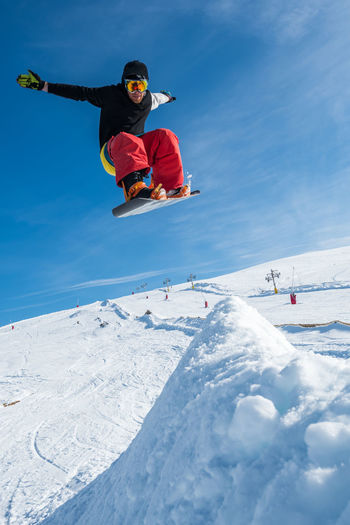 Man jumping with snowboard on landscape