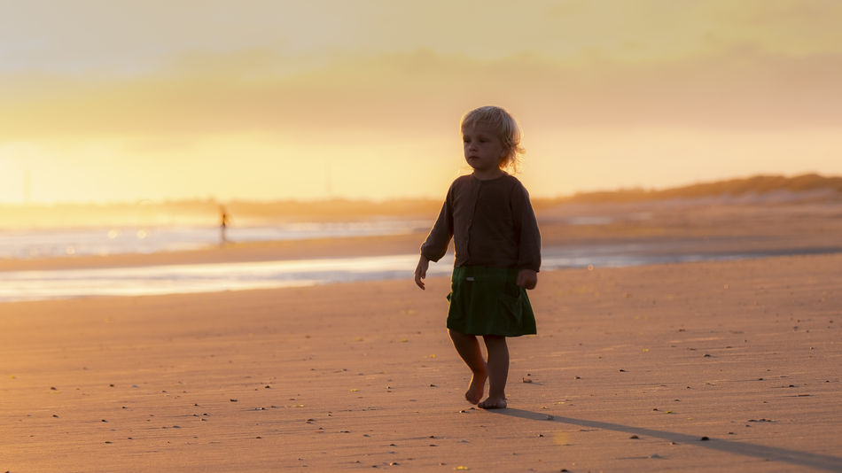 Little girl in the sunset. Vacations Beach Beauty In Nature Child Childhood Childhood Memories Full Length Horizon Over Water Innocence Land Leisure Activity Lifestyles Nature One Person Outdoors Real People Rear View Sand Scenics - Nature Sea Sky Sunset Water