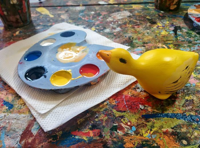 High angle view of rubber duck with palette and tissue paper on table