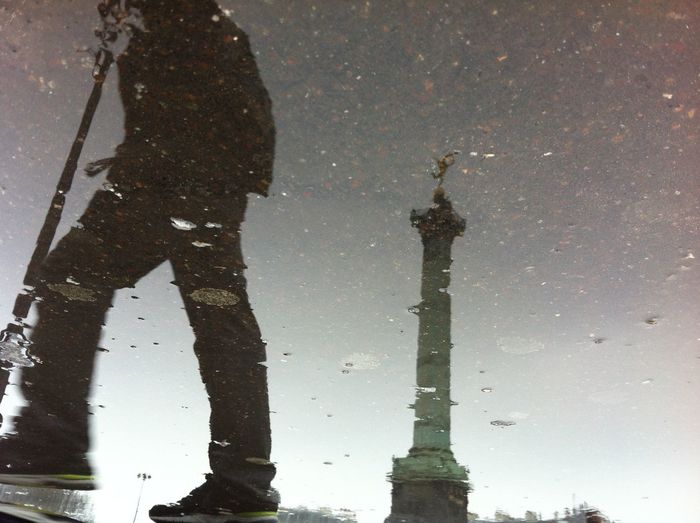 Upside down image of person and berlin victory column reflecting in puddle
