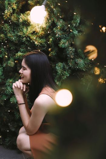 Side view of woman looking at illuminated tree