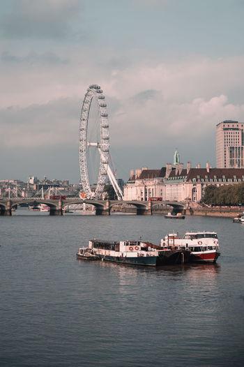 Scenic view of ferris wheel in city against sky