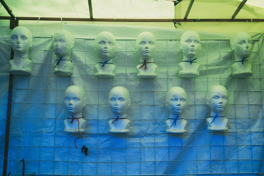 Heads of mannequins installed in a street stall. Human Representation Representation No People Sculpture Art And Craft Male Likeness Architecture Statue Blue Built Structure Day Creativity Low Angle View Side By Side Female Likeness Retail  Indoors  Glass - Material Window