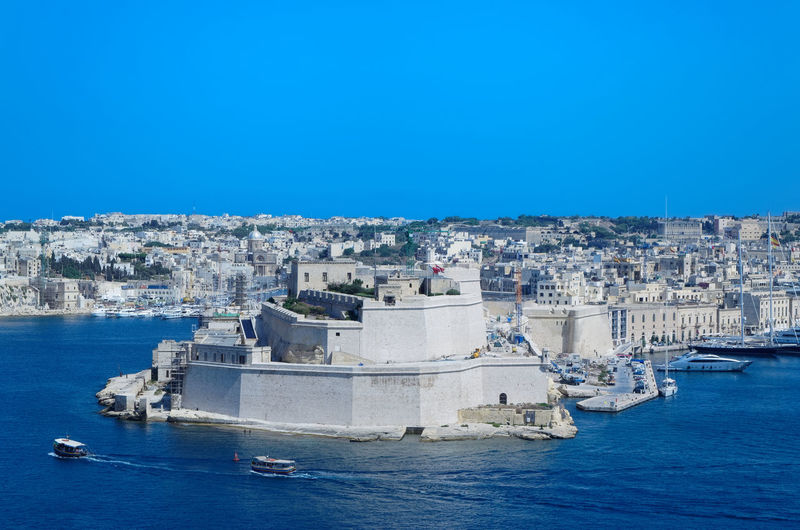 Limestone walls and towers of fort st angelo in malta. view from upper barrakka gardens in valletta