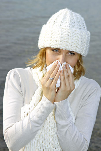 Woman with cold snuffs into a tissue Autumn Catched A Cold Tissue Walk Winter Woman Best Age Close-up Cold Cold Temperature Day Facial Tissue Illness Lake One Person Outdoors People Portrait Sick Snuffs Warm Clothing Water Winter Young Adult Young Women