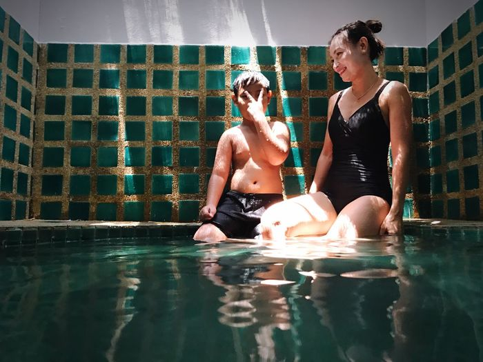 Young woman sitting with son in swimming pool