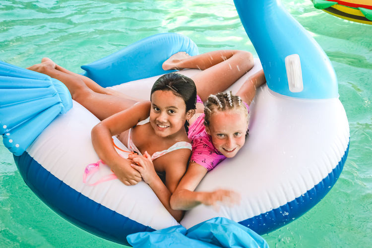 friendship and fun summer in the pool, childhood, girls, play, inflatables Childhood Child Pool Water Swimming Pool Two People Girls Women Togetherness Happiness Inflatable  Portrait Emotion Smiling Real People Females Looking At Camera Family Innocence Floating On Water Diversity Friendship Vacations