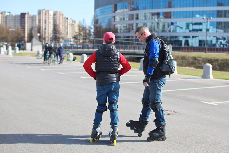 Architecture Bonding Casual Clothing Child Childhood City Day Full Length Jeans Leisure Activity Males  Men Outdoors People Real People Rear View Road Roller Skate Street Togetherness Transportation Two People