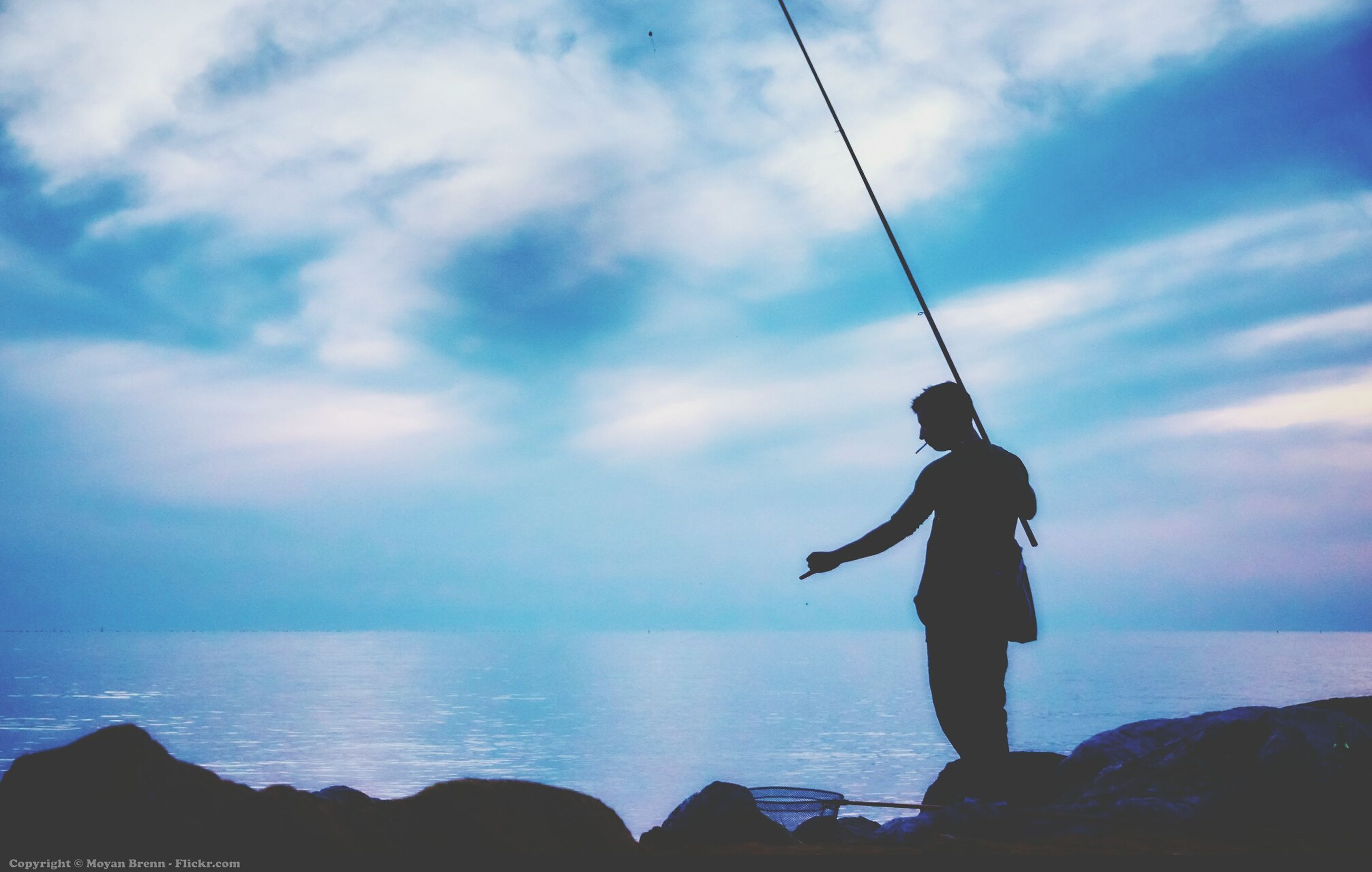 full length, sky, lifestyles, sea, leisure activity, men, water, standing, horizon over water, silhouette, cloud - sky, rear view, scenics, beauty in nature, fishing rod, holding, nature, tranquility