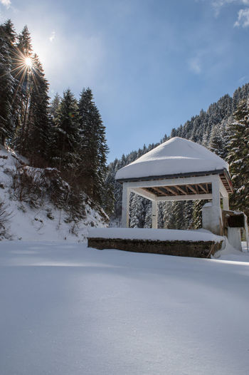 Built structure on snow covered land and trees against sky