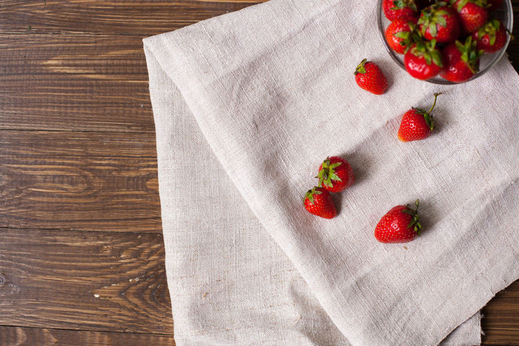 Full glass bowl of fresh ripe srawberries and kitchen towel with delicious strawberries on it Berry Fruit Close-up Food Food And Drink Freshness Fruit Healthy Eating Indoors  Leaf No People Red Strawberry Tablecloth Towel White Wood - Material