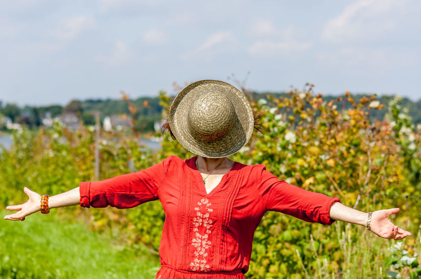 woman with hat and arms outstretched in front of the wine grape Field Grapevine Hat Wine Grape Woman Adult Arms Outstretched Beauty In Nature Casual Clothing Focus On Foreground Grass Human Body Part Human Hand Leisure Activity Nature One Person Outdoors Outstretched Arms Real People Red Sky Standing Wine Grape Field Woman Portrait Young Adult Mix Yourself A Good Time The Week On EyeEm The Week On EyeEm
