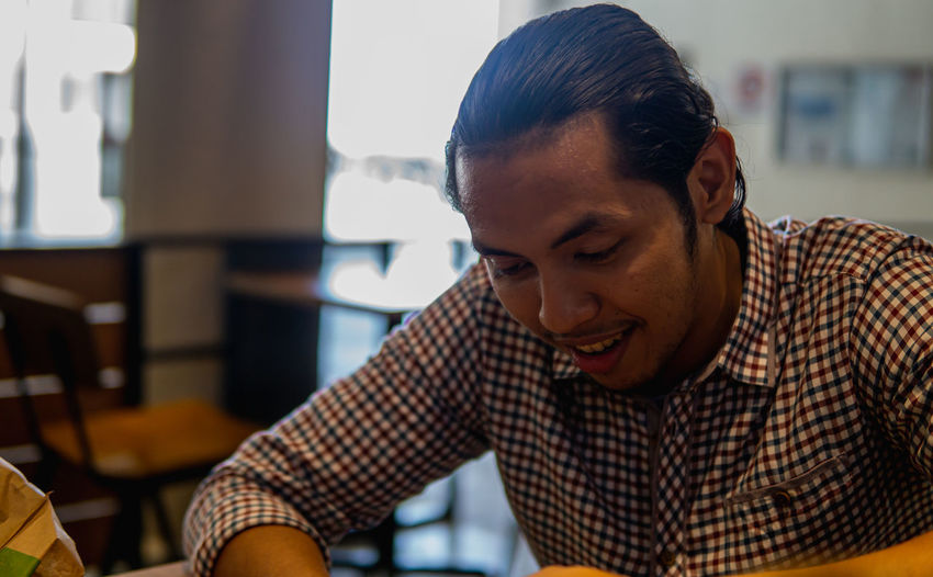 A portrait of young asian malay businessman sitting inside of cafe and looking at phone.