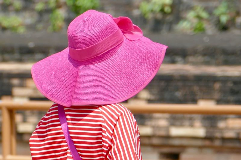 Woman wearing pink hat standing outdoors