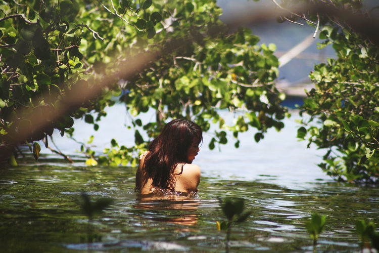 Rear view of topless woman swimming in lake
