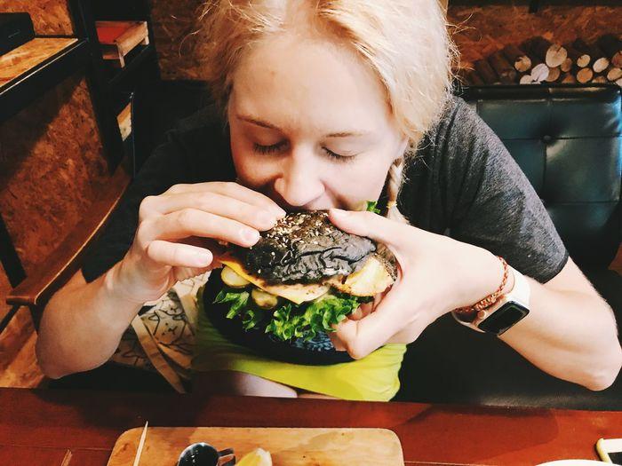 High angle view of woman eating hamburger at restaurant