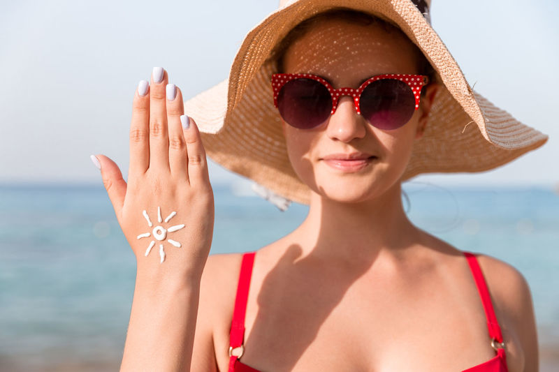 Portrait of woman wearing sunglasses with lotion standing against sea