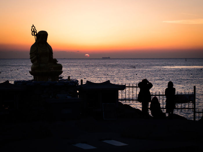 Silhouette of woman at seaside during sunset