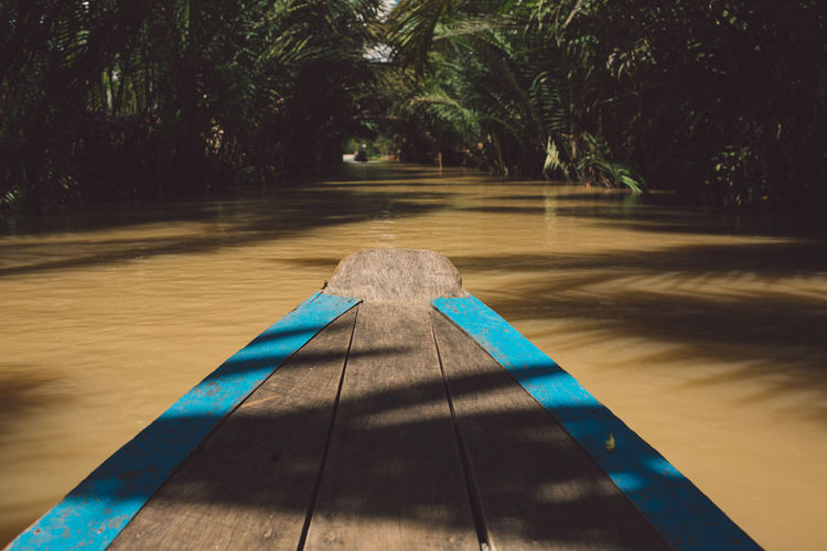 Wooden rowboat in river at forest