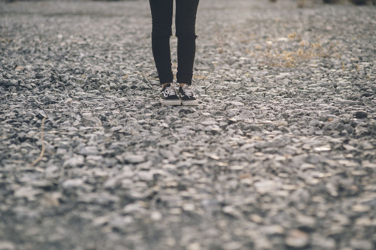 photo of the legs of a lonely young woman dressed in jeans and black sneakers standing on a stone floor in the countryside Adult Body Part City Day Human Body Part Human Foot Human Leg Human Limb Jeans Leisure Activity Lifestyles Low Section One Person Outdoors Real People Selective Focus Shoe Standing Street Surface Level Unrecognizable Person Walking Women