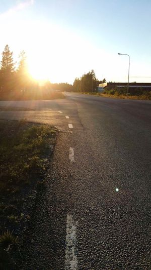 Sunlight Sunset Lens Flare Sun Sunbeam Road Transportation Outdoors Nature Sky The Way Forward Tree Landscape Grass Day Beauty In Nature Luleå  No People Clear Sky